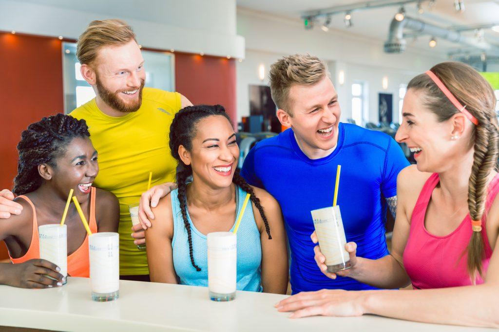 Frauen und Männer trinken zusammen einen Shake