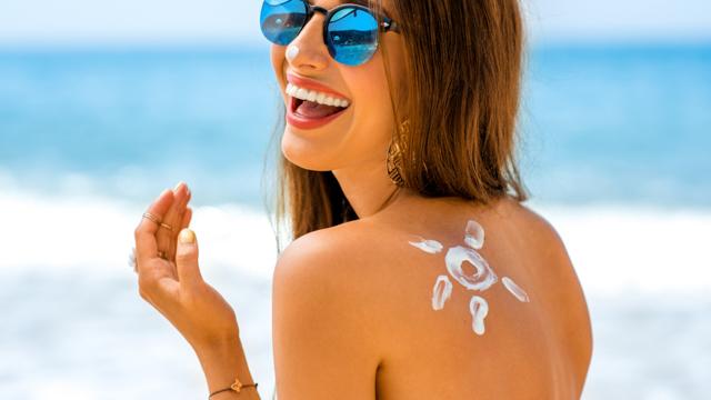 Frau in der Sonne mit Sonnencreme